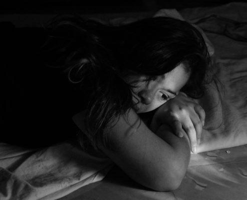 depressed woman laying in bed awake