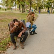 man and woman sitting on opposite park bench sides breaking up
