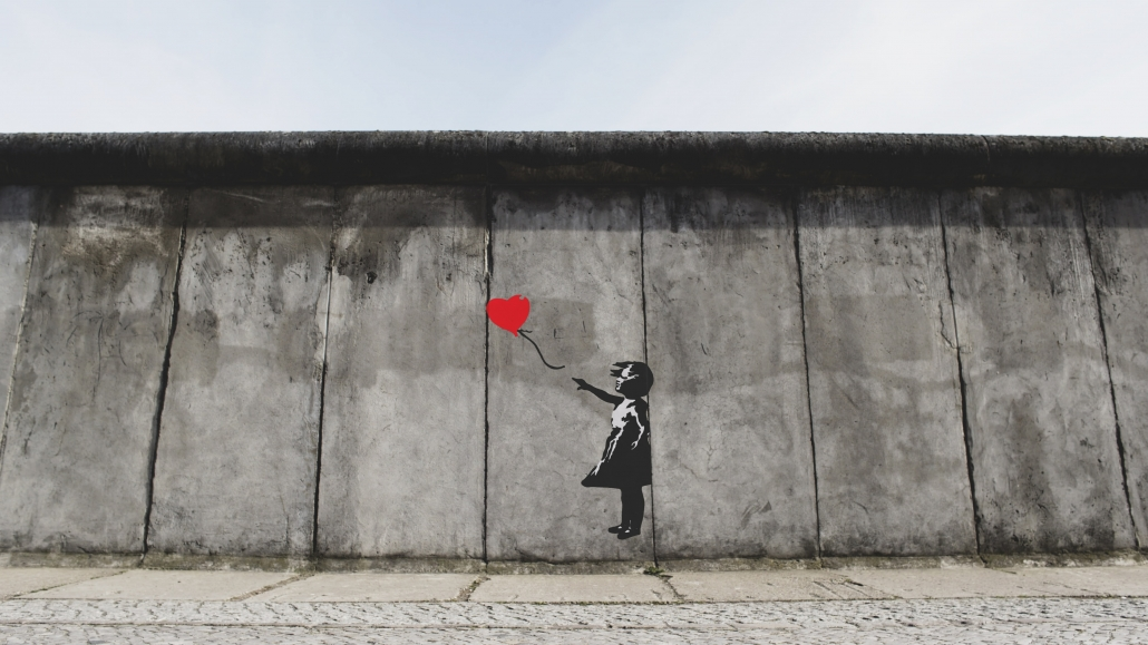 wall mural of girl letting heart balloon go
