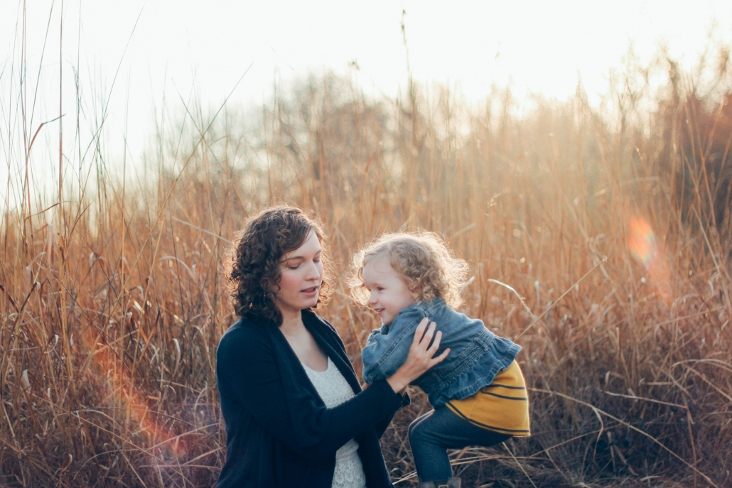 mom holding toddler daughter in field