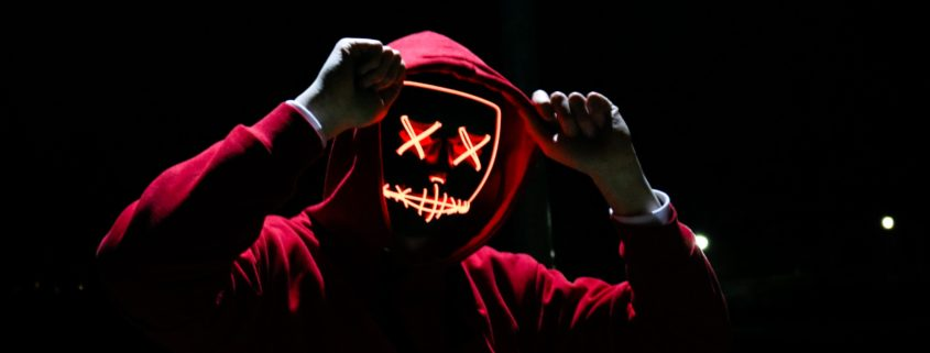 man in hoodie in dark with Xs for eyes
