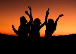 women at sunset celebrating