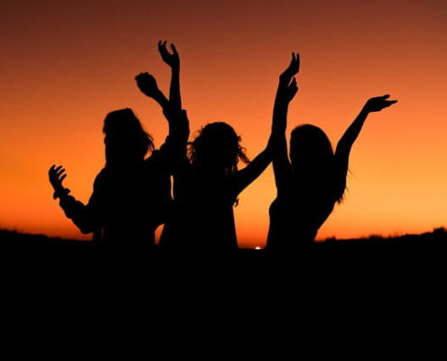 women at sunset celebrating