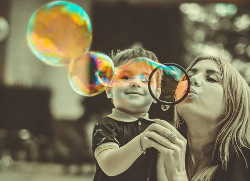 mom blowing bubble for son