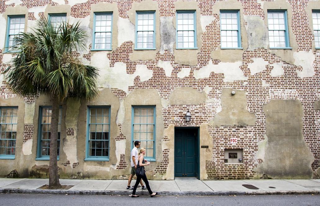 man and woman walking near Charleston building
