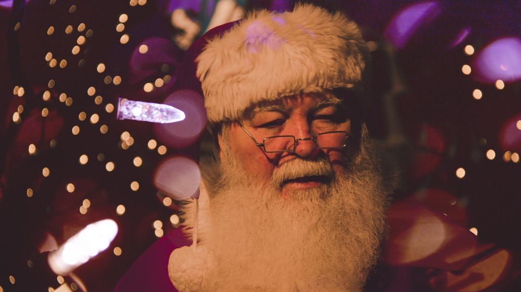 santa next to a christmas tree